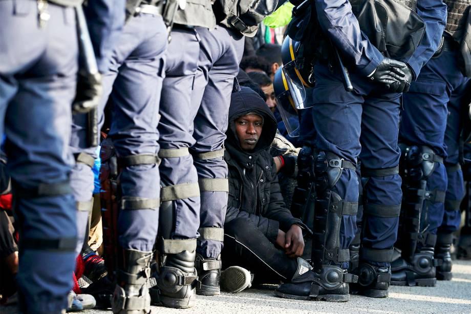 Policiais franceses ficam próximos de migrantes, durante operação de evacuação do acampamento improvisado de refugiados em Calais - 25/10/2016