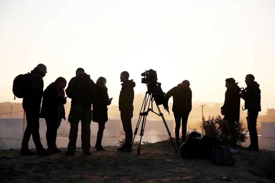 Jornalistas trabalham próximos ao acampamento improvisado de refugiados localizado em Calais, na França - 25/10/2016