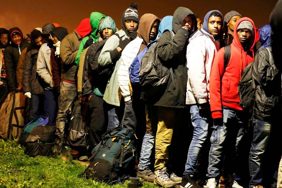 Migrantes aguardam para serem transferidos para centros de acolhimento, após evacuação do acampamento improvisado de refugiados localizado em Calais, na França - 24/10/2016