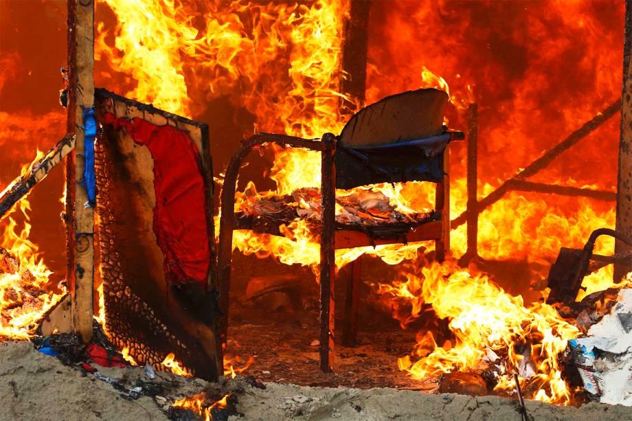 Chamas incendeiam cadeira dentro de abrigo localizado no campo de Calais, na França, durante o terceiro dia de evacuação do local - 26/10/2016