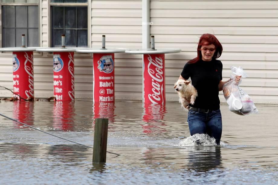 Mulher carrega seu cão no colo enquanto caminha em uma rua inundada após a passagem do furacão Matthew em Garden City, no estado americano da Georgia - 08/10/2016