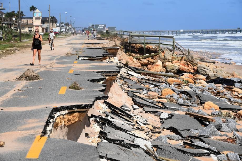 Residentes caminham sobre uma rodovia danificada após a passagem do furacão Matthew em Flagler Beach, na Flórida (EUA) - 08/10/2016