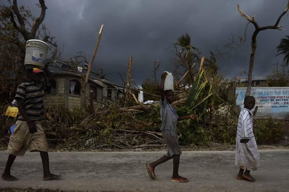 Pessoas carregam água em Port-Salut, ao sudoeste da capital Porto Príncipe no Haiti. Após a passagem do furacão Matthew, um surto de cólera é mais uma ameaça à vida da população do país caribenho - 09/10/2016