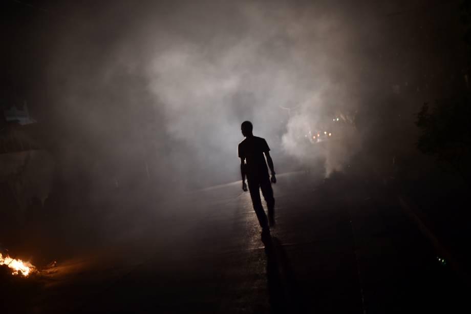 Homem caminha através da fumaça da queima de detritos deixados pelo furacão Matthew, em Les Cayes, no sudoeste do Haiti - 09/10/2016