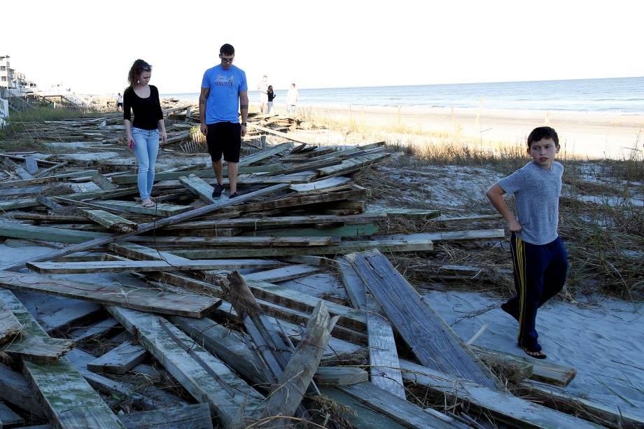 Pessoas caminham entre os destroços de um cais danificado pelo furacão Matthew em Surfside Beach, no estado americano da Carolina do Sul - 09/10/2016