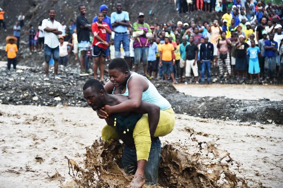 Homem carrega mulher ao atravessar rio durante a passagem do furacão Matthew no Haiti - 05/10/2016