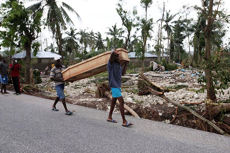 Homem carrega caixão com vítima do furacão Matthew, em Cavaillon, no Haiti - 06/10/2016