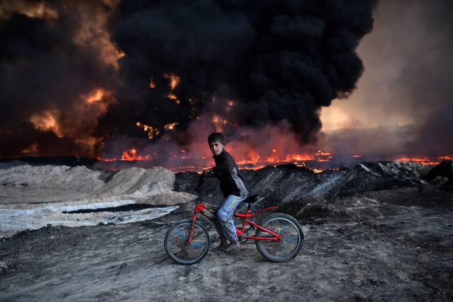 Garoto é fotografado em frente a um campo de petróleo incendiado, durante ofensiva do exército iraquiano contra o Estado Islâmico em Mosul - 21/10/2016