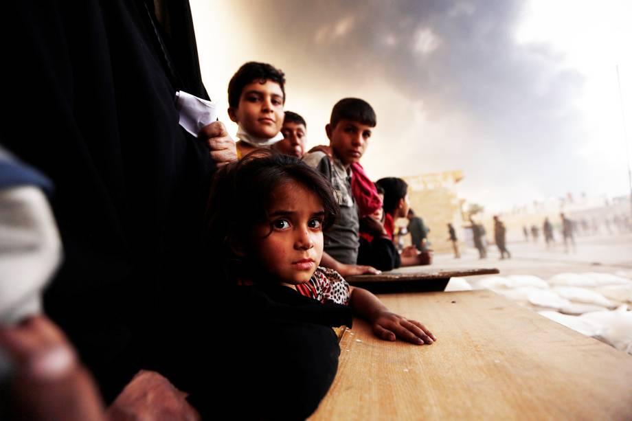 Desabrigados aguardam por alimentos durante a ofensiva militar iraquiana na cidade de Qayyara, ao sul de Mosul - 21/10/2016