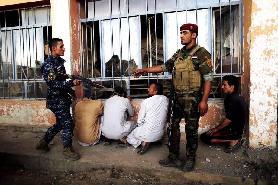 Soldados iraquianos revistam suspeitos de serem militantes do grupo extremista Estado Islâmico, em Qayyara, ao sul de Mosul - 21/10/2016