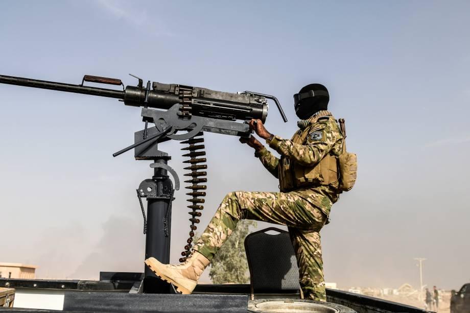 Membro das forças iraquianas com uma metralhadora em cima de um veículo blindado, enquanto se dirige para a linha de frente durante operação para retomada da cidade de Mosul das mãos do Estado Islâmico - 18/10/2016