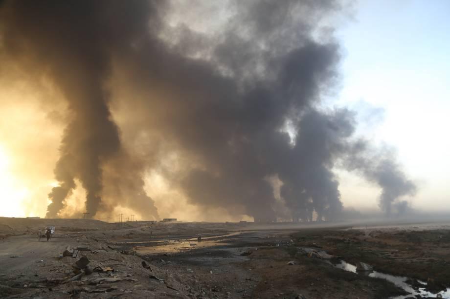 Exército iraquiano chega na vila Hut enquanto a fumaça sobe dos poços de petróleo incendiados por terroristas do Estado Islâmico para limitar o avanço das forças de coalizão em direção a Mosul - 18/10/2016