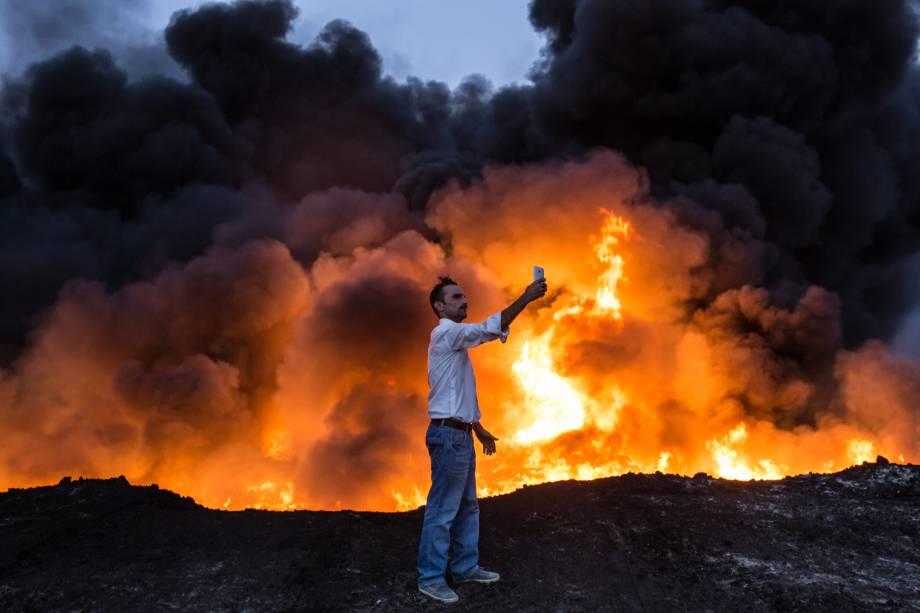 Homem faz uma selfie em frente a poço de óleo incendiado em Qayyarah, ao sul de Mosul - 19/10/2016