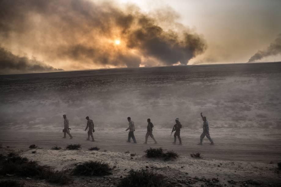 Soldados iraquianos caminham em uma estrada enquanto uma coluna de fumaça é vista ao fundo, em Qayyarah, ao sul de Mosul - 19/10/2016