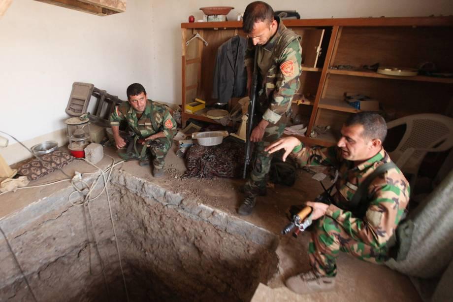 Membros das forças curdas, conhecidos como peshmergas, observam um túnel construído por militantes do Estado Islâmico, em Bartila, leste de Mosul - 19/10/2016
