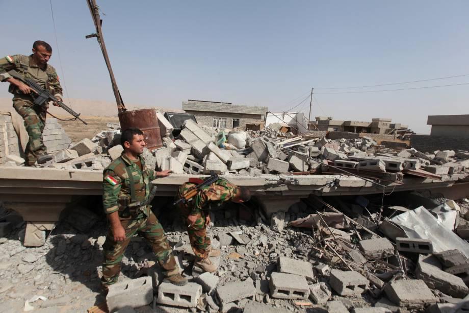 Membros das forças curdas, conhecidos como peshmerga, observam casas destruídas por militantes do Estado Islâmico, na periferia de Bartila, leste de Mosul - 19/10/2016