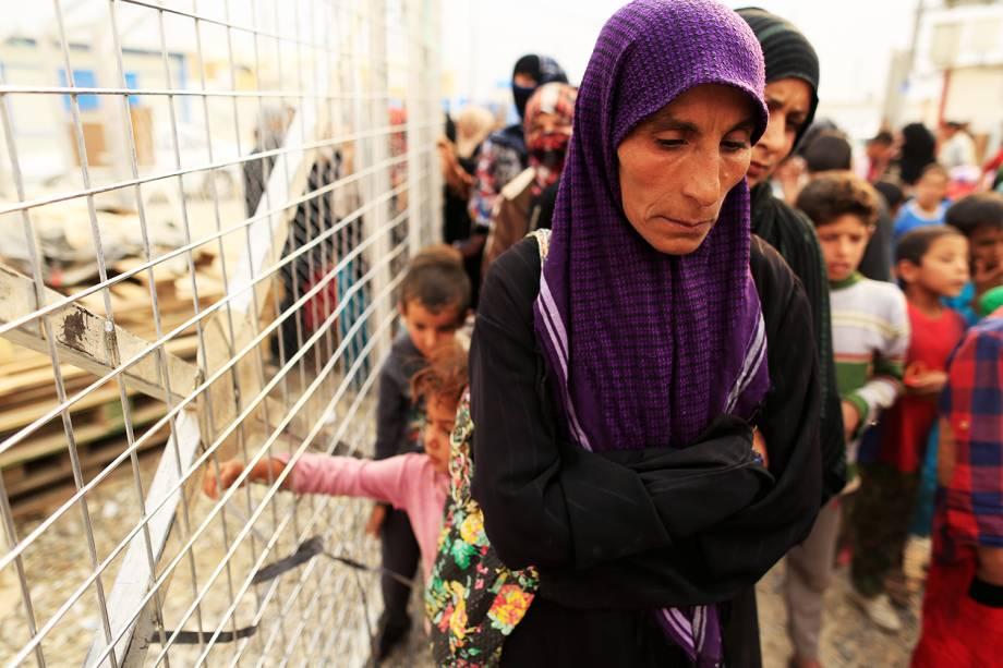 Mulher espera em fila para receber cobertores e colchões, em acampamento para desabrigados durante a ofensiva militar em Mosul, no Iraque - 24/10/2016