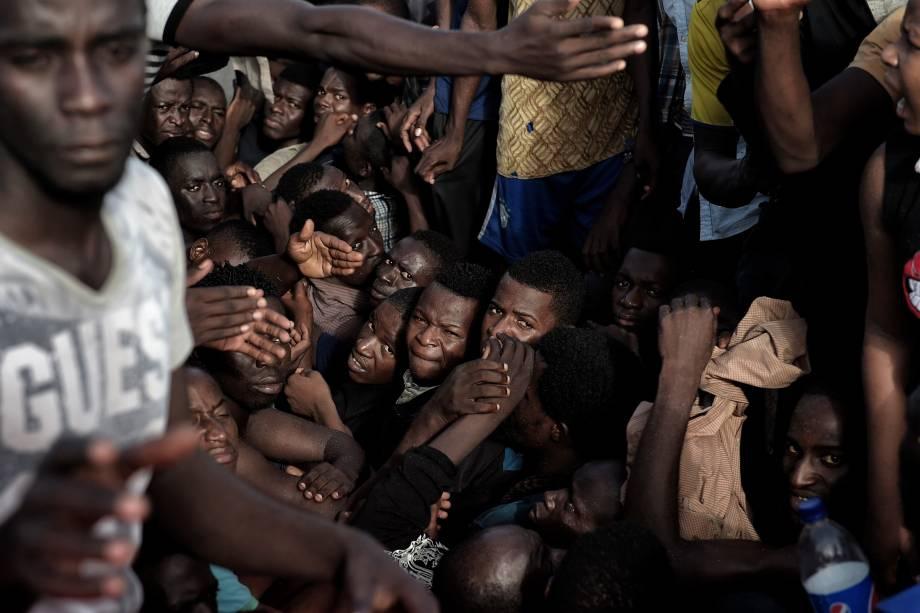 Imigrantes aguardam por resgate em uma embarcação superlotada e à deriva no Mar Mediterrâno, ao norte da costa Líbia