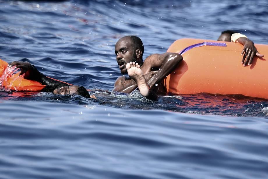 Imigrantes se agarram em boias enquanto esperam para serem resgatados no Mar Mediterrâneo