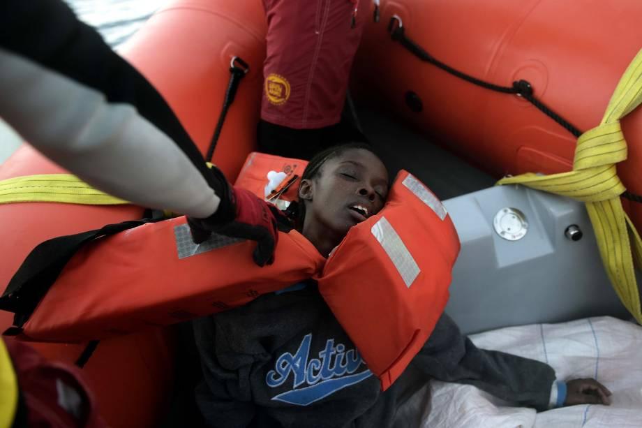 Mulher desmaia após ser resgatada de uma embarcação superlotada de imigrantes e refugiados no Mar Mediterrâneo