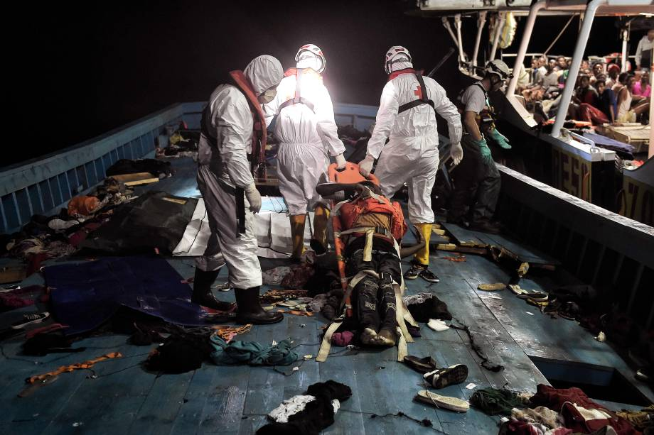 Membros da organização humanitária Proactiva Open Arms retiram o corpo de um imigrante de uma das embarcações durante operação de resgate no Mar Mediterrâneo