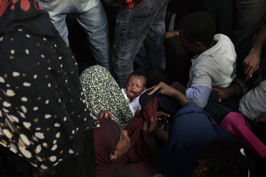 Criança chora no colo de sua mãe enquanto dezenas de imigrantes e refugiados aguardam pelo resgate em um barco à deriva no Mar Mediterrâneo