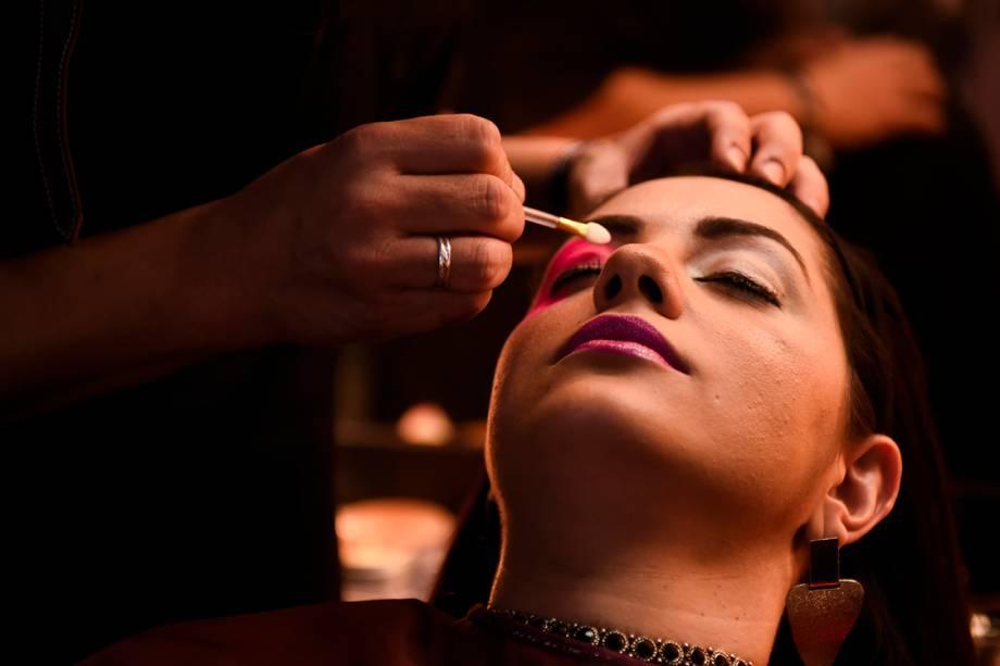 Mulher é maquiada durante a São Paulo Fashion Week
