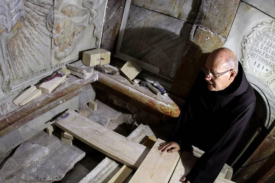 Frei Franciscano observa o local em que Jesus Cristo teria sido sepultado, segundo a tradição cristã. Após a remoção das placas de mármore, foi possível encontrar, intacta, a cama funerária onde acredita-se que o corpo teria sido colocado.