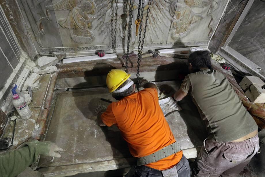 Equipe de especialistas limpa a superfície de uma das placas de mármore que cobria o local que, acredita-se, seja o túmulo de Jesus.
