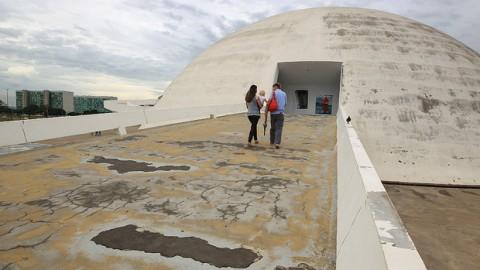 """Localizado entre a Catedral e o Congresso Nacional, o Museu Nacional da República é um dos monumentos mais recentes de Oscar Niemeyer e destaca-se como um dos pontos imprescindíveis no roteiro de turistas interessados nas obras do arquiteto. Ao chegar ao local, porém, os turistas vão se deparar com um ambiente inóspito: a cúpula do museu está imunda e a famosa rampa de acesso, além da sujeira, apresenta rachaduras. Pior: os arredores de uma das principais referências da capital do país virou ponto de tráfico de drogas e atrai usuários à luz do dia. """"Às 15h já podemos ver os consumidores"""", conta um dos seguranças, que preferiu não se identificar. Ele reclamou ainda da falta de segurança e da ausência de policiamento no local."""
