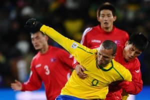 Luis Fabiano disputa bola com jogadores norte-coreanos durante jogo da fase de grupos da Copa do Mundo de 2010