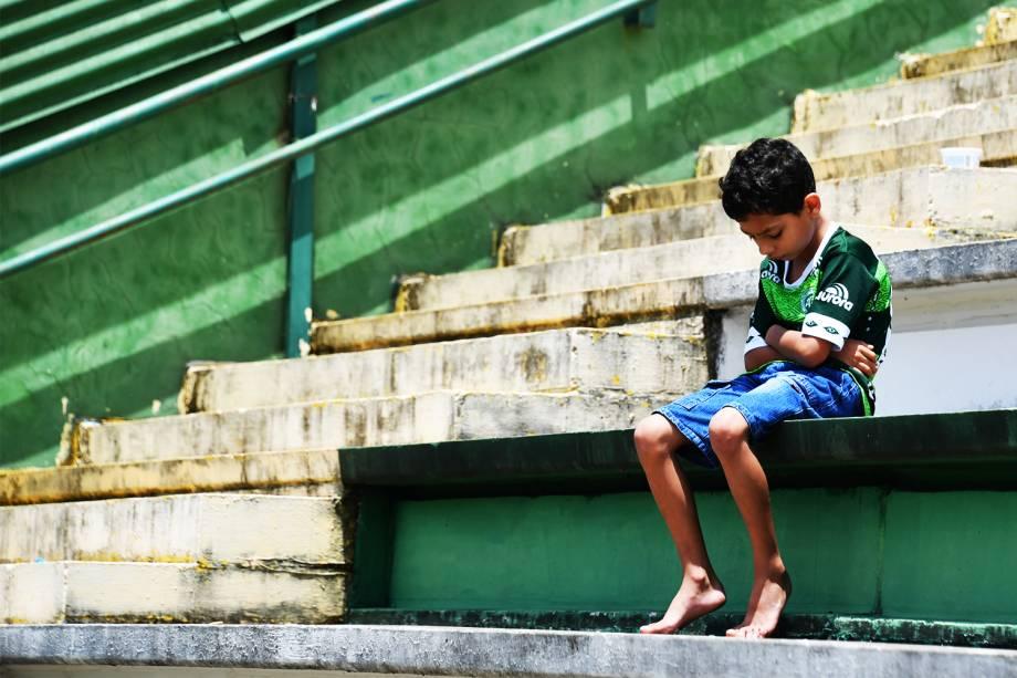 Torcedor mirim da Chapecoense senta sozinho nas arquibancadas da Arena Condá em Chapecó (SC) , durante homenagens às vítimas do acidente aéreo na Colômbia