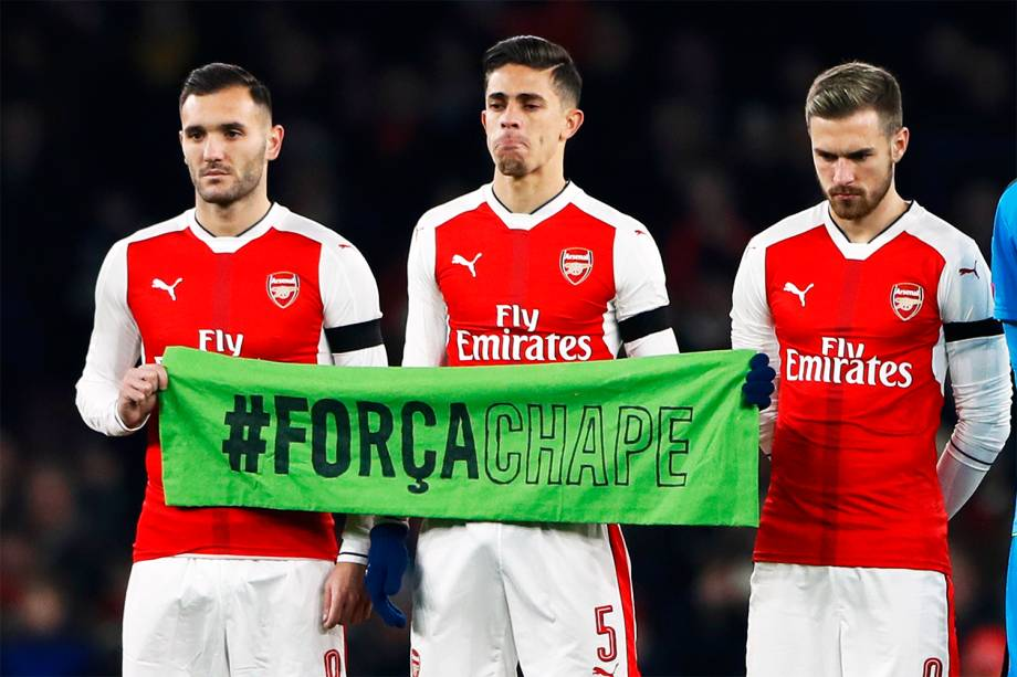 Os jogadores do Arsenal, Lucas Perez, Gabriel Paulista e Aarom Ramsey seguram faixa com a hashtag '#ForçaChape', em homenagem às vítimas do voo que transportava a equipe catarinense - 30/11/2016