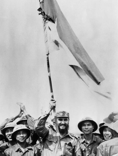 Fidel Castro levanta a bandeira do Vietnã durante visita ao país enquanto ocorria a guerra do Vietnã contra os Estados Unidos, em 1973