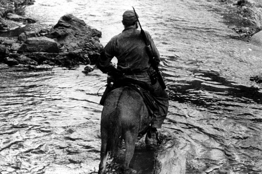 Fidel Castro tenta atravessar um riacho em cima de seu cavalo em Sierra Maestra, leste de Cuba, onde avançava com seu exército na tentativa de depor o ditador Fulgencio Batista, em dezembro de 1958