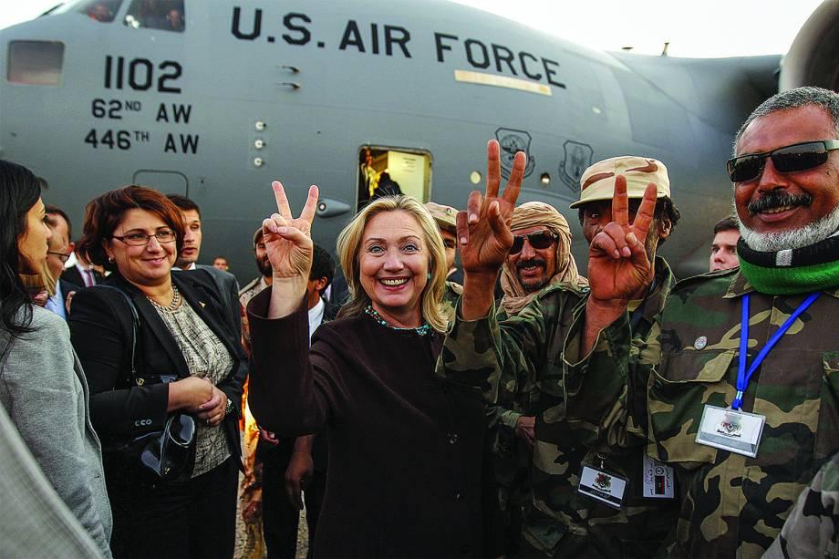 A secretária de Estado norte-americana Hillary Clinton (C) gesticula com os soldados líbios após sua partida de Trípoli, na Líbia - 18/10/2012