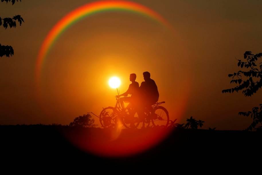 Garotos andam de bicicleta durante pôr-do-sol na cidade de Agartala, Índia - 21/11/2016