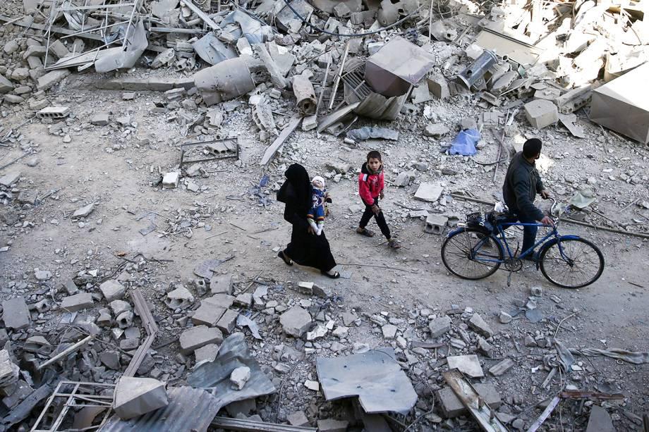 Pessoas andam através dos escombros de edifícios destruídos por ataques aéreos no bairro rebelde de Douma, em Damasco, na Síria - 18/11/2016
