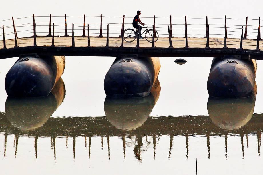 Ciclista atravessa ponte improvisada sobre o rio Ganges, em Allahabad, na Índia - 07/11/2016