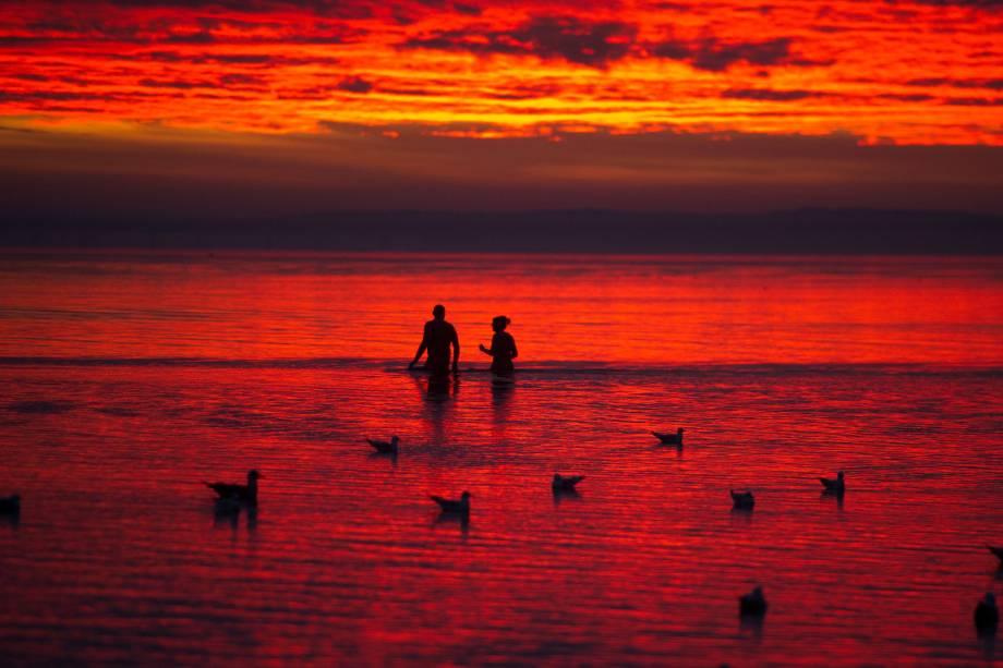 Pessoas e as gaivotas se banham durante o amanhecer em Stralsund perto da ilha alemã de Rügen, no mar Báltico - 23/11/2016
