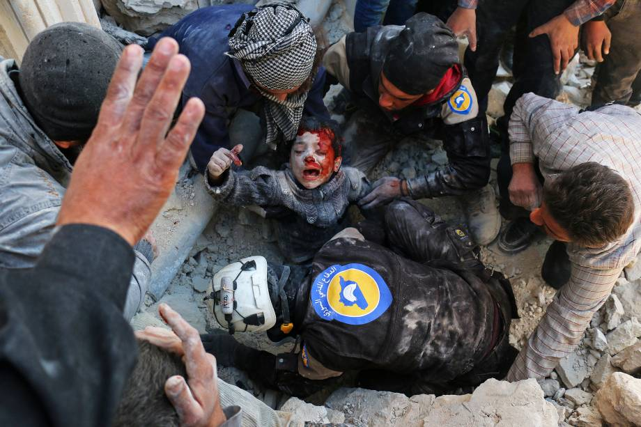 Voluntários da defesa civil, conhecidos como os Capacetes Brancos, resgatam um menino dos escombros após um ataque a bomba no bairro de Bab al-Nairab, em Alepo, norte da Síria - 24/11/2016