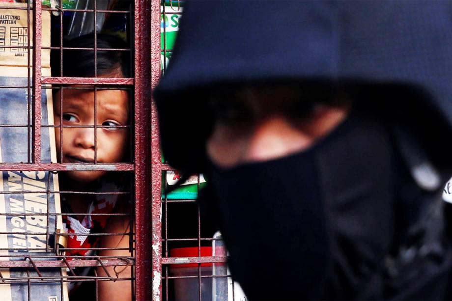 Garota observa através de janela, membro da Polícia Nacional Filipina em operação anti-drogas, na cidade de Pasig - 09/11/2016