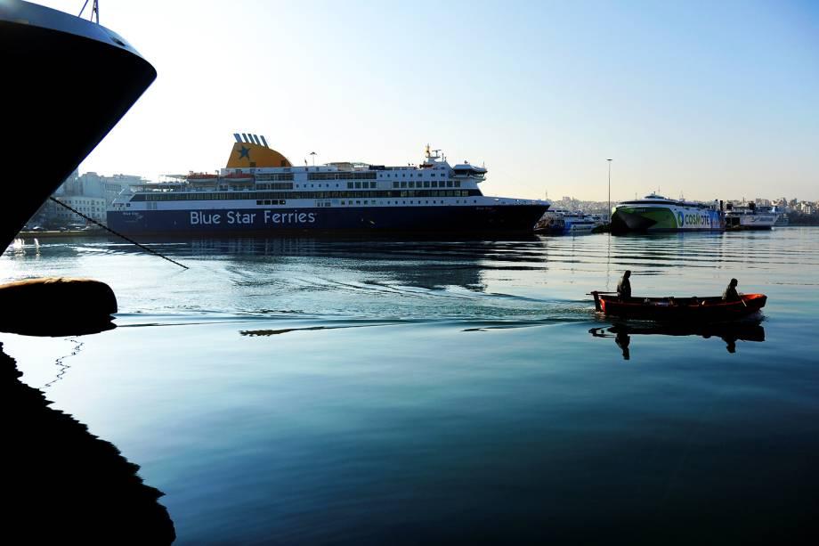 Um barco passa por navios de passageiros em greve dos trabalhadores navais, que protestam contra as políticas governamentais que afetam o setor, no porto de Pireu, em Atenas, na Grécia - 24/11/2016