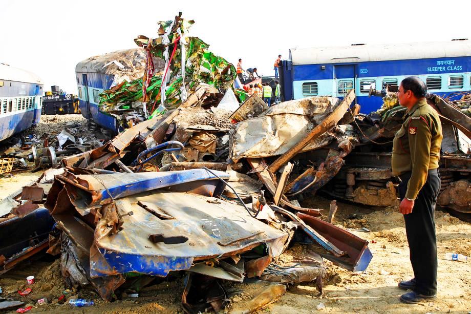 Policial observa destroços de trem que descarrilou em Pukhrayan, na Índia, causando a morte de mais de 100 pessoas - 21/11/2016