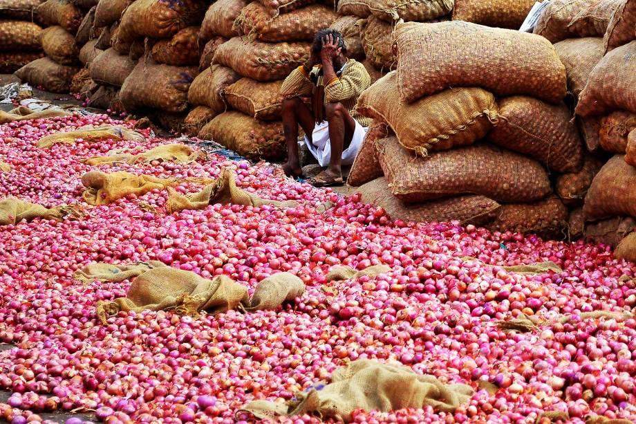 Vendedor de cebolas aguarda clientes em um mercado de Bengaluru, na Índia - 21/11/2016
