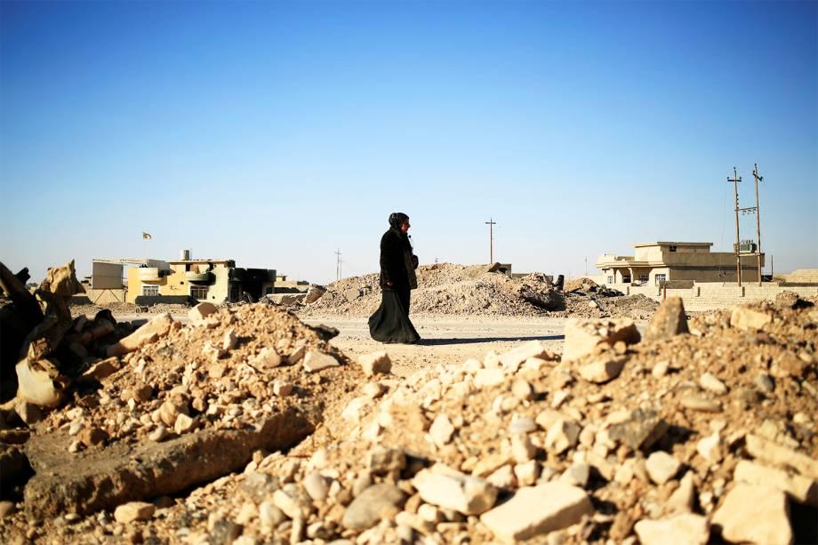 Mulher caminha próxima a um posto de controle de militares iraquianos no leste de Mosul, durante ofensiva militar contra o grupo extremista Estado Islâmico - 03/11/2016