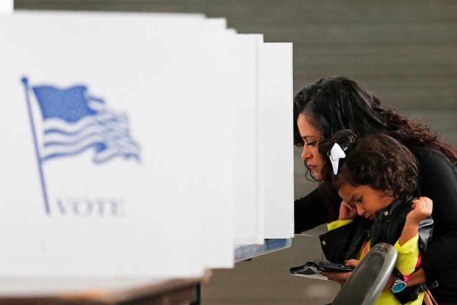 Mulher vota em cabine com sua filha em Smithfield, no estado americano da Carolina do Norte - 08/11/2016
