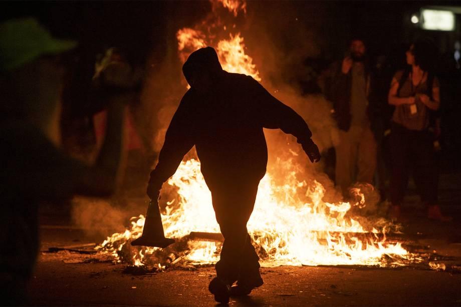 Manifestante lança cone em barricada incendidada, em protesto contra a vitória do republicano Donald Trump nas eleições presidenciais americanas - 09/11/2016