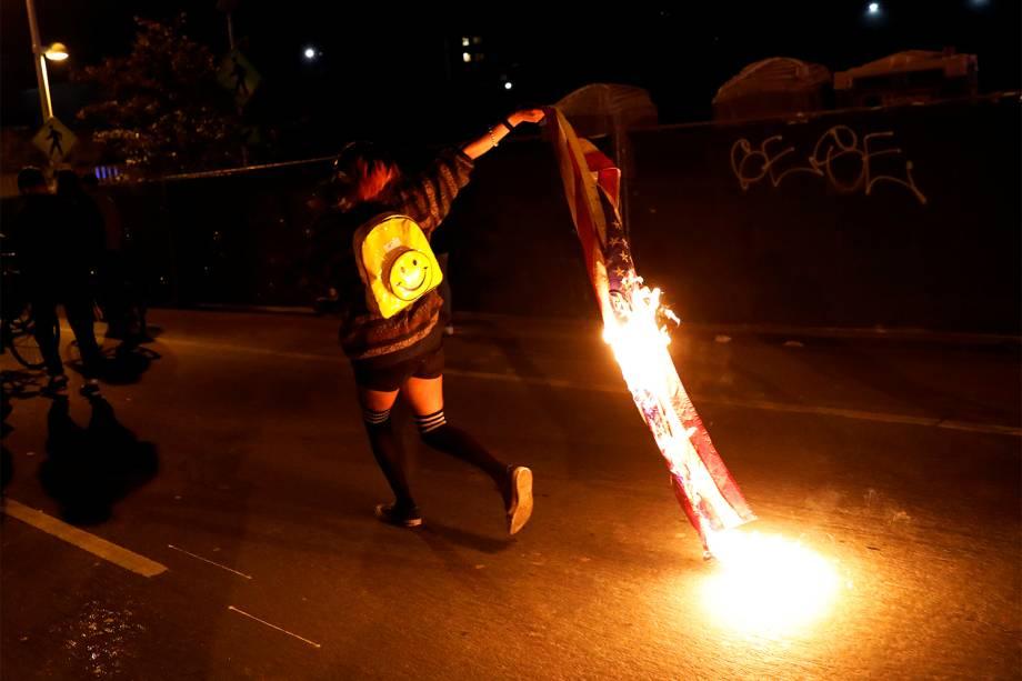 Manifestante queima bandeira dos Estados Unidos em protesto contra a vitória do republicano Donald Trump nas eleições presidenciais americanas, na cidade de Oakland, Califórnia - 10/11/2016