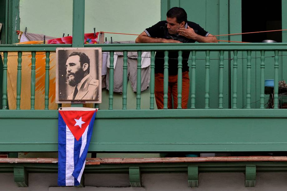 Homem exibe retrato do líder revolucionário Fidel Castro e a bandeira cubana, em uma sacada da cidade de San Francisco de Asis, em Havana - 27/11/2016